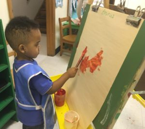 Boy painting at an easel