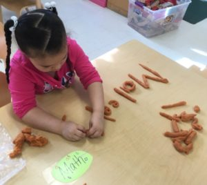 Girl spelling her name with playdough